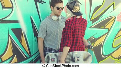 Young trendy couple chatting at a skate park