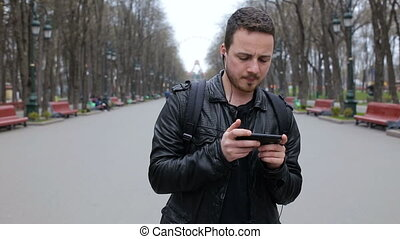 Young trendy man listen to music on smartphone in city park and dance
