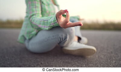 Young trendy woman meditating in lotus pose sitting on empty...