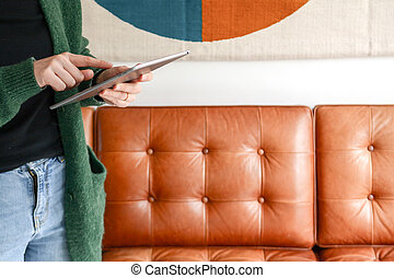 Young trendy woman using tablet device at home with fashionable interior