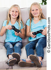 Young twins playing video games tog