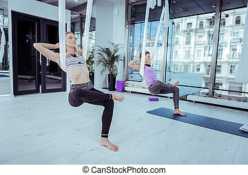 Young two woman finding balance during yoga - No gravity....