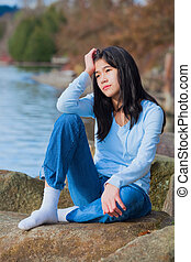 Young unhappy teen girl sitting on rocks along lake shore, looking off to side, head in hand