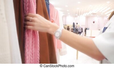 Young unrecognizable woman choosing clothing in a store close up video