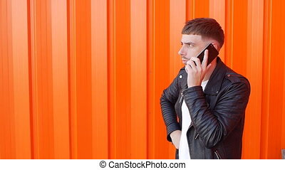 Young unshaven caucasian guy in a black jacket emotionally talking on the phone and is angry at the orange background, slow-mo