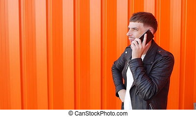 Young unshaven caucasian guy in a black jacket emotionally talking on the phone and is angry at the orange background, slow-mo, fashionable