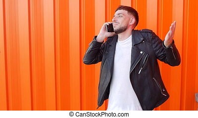 Young unshaven caucasian man in a black jacket emotional talking on the phone on an orange background, slow-mo, fashionable