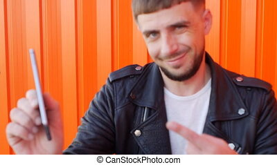 Young unshaven caucasian man in a black jacket talking on the phone on an orange background, slow-mo, fashionable