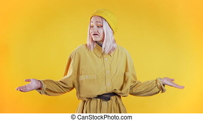 Young unsure girl shrugs her arms, makes gesture of I don't know, care, can't help anything .Young millenial woman on yellow background