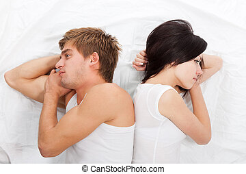 young upset couple in bed