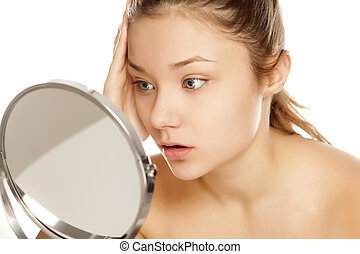 young upset girl looking her self in the mirror
