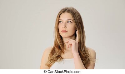 Young upset thoughtful woman smiles on the white background slow motion