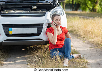 Young upset woman crying because of broken car calling auto service for help