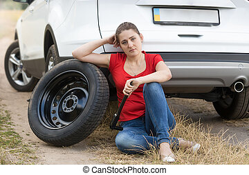 Young upset woman sitting on ground leaning on broken car
