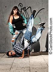 Young urban couple dancers hip hop dancing urban scene