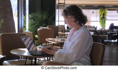 Remote office concept. Making money background. Woman with laptop sitting in the cafe. Successful woman combining work and vacation. Work and vacation concept. Female typing at laptop