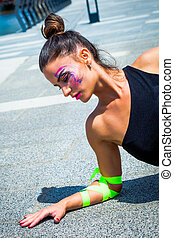 young urban finess woman with artistic makeup outdoor in the city summer day