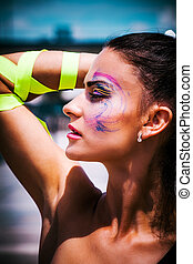 young urban finess woman with artistic makeup outdoor in the city sunny summer day