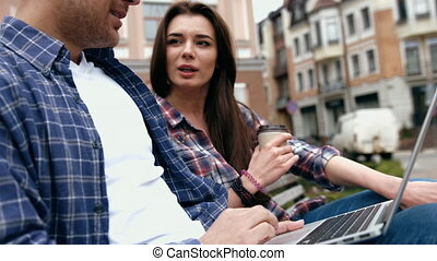 Young urban people in checkered shirts and blue jeans using...