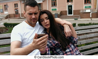 Young urban people man wearing white T-shirt and woman in checkered shirt with phones sitting on a bench