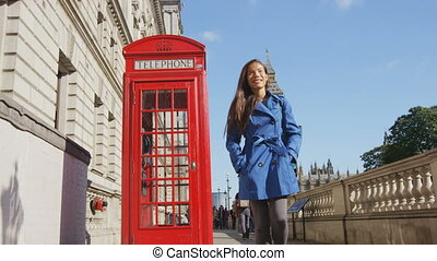 Young female urban professional by red telephone booth and Big Ben in London, England, Great Britain. Casual business woman in trench coat walking in street enjoying leisure time in United Kingdom.
