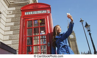 Young female urban professional taking selfie using mobile smart phone by red telephone booth in London, England, Great Britain. Happy young woman is walking by Big Ben enjoying leisure time in UK.