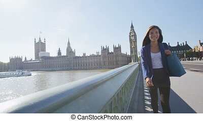 Young urban professional woman walking in London with purse after shopping