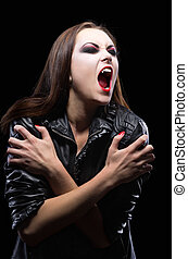Young vampire girl isolated on black