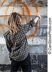 Young vandal drawing graffiti