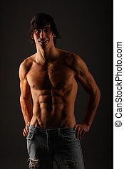 Young very muscular half-naked male standing in a pair of...