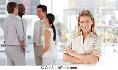 Business woman in front of a group of associates smiling