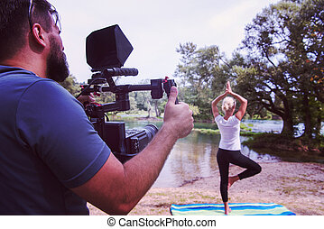 young videographer recording while woman doing yoga exercise