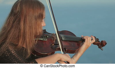 Young violinist in tracery dress plays on a rock by the sea