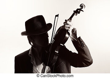 young violinist playing the violin in hat and jacket  on a light background