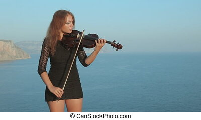 Young violinist plays with inspiration by the sea - Young...