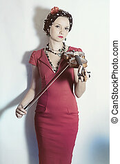 Young violinist woman with violin in hands