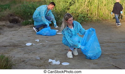 Young volunteers and children collecting garbage in park on the river Bank.