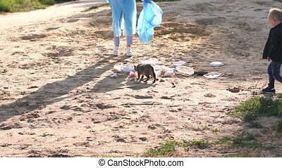 Young volunteers and children collecting garbage on beach, a cat on the beach.