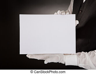 Closeup Of Young Waiter Presenting Blank Placard Over Black Background