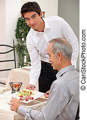 Young waiter serving an older customer