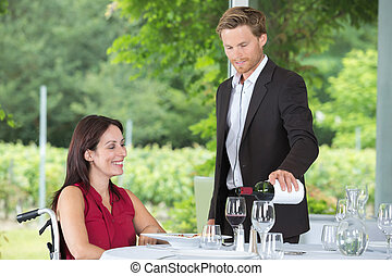 young waiter serving mature disabled woman at the restaurant