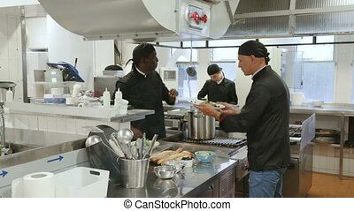 waitress taking prepared dishes from chef in kitchen of modern restaurant