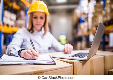 Young warehouse worker with laptop working.