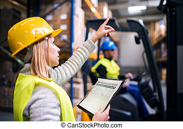 Young warehouse workers working together. Man sitting in a forklift and woman holding notes, checking something.