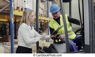 Young warehouse workers working together. Man sitting in a...