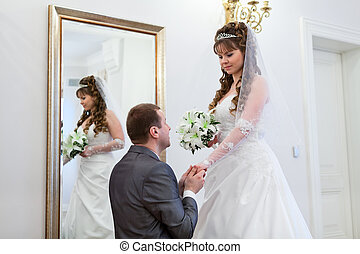 Young wedding Caucasian Russian couple. Groom kissing hand of bride