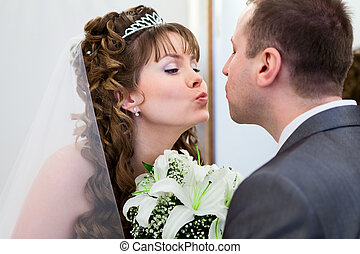 Young wedding Caucasian Russian couple kissing together and flowers between