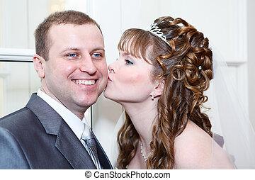 Young wedding Caucasian Russian couple. Bride kissing groom in cheek