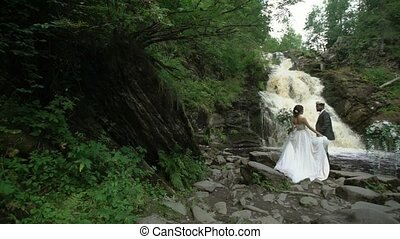 Young wedding couple at ceremony near waterfall