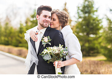 Young wedding couple enjoying romantic moments outside on autumn nature